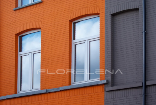 Two windows on orange brick wall. Urban background